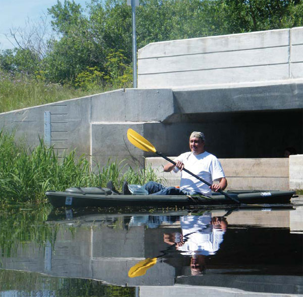 ANISHINAABE SCIENTIST. Michael Price kayaks at the Wild Rice River dam while preparing to take students out on Lower Rice Lake to collect data on wild rice stands. Photo courtesy of Michael Price