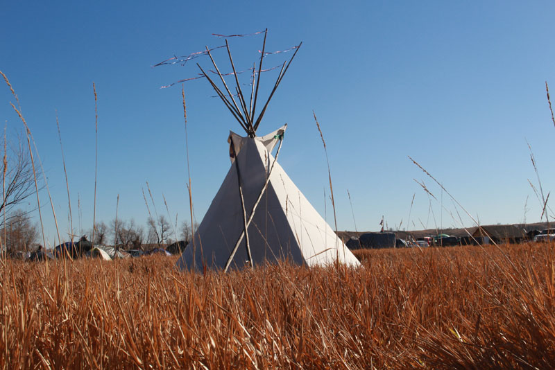 TIPI AT CAMP OCETI UNDER A BLUE SKY